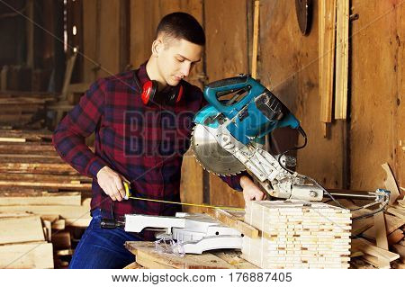 Workman Dressed In The Checkered Shirt Working With Tape-measure Near Circular Saw. Timbers On Backg
