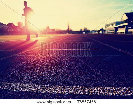 Tall Man Running On Red Running Racetrack On The Stadium.