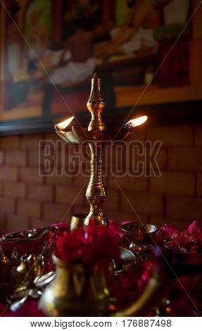 KERALA, INDIA. The burning lamp - the sacred fire of the Hindus and offerings to Lord Shiva on the tray. Chowara, Kerala, South-west India.