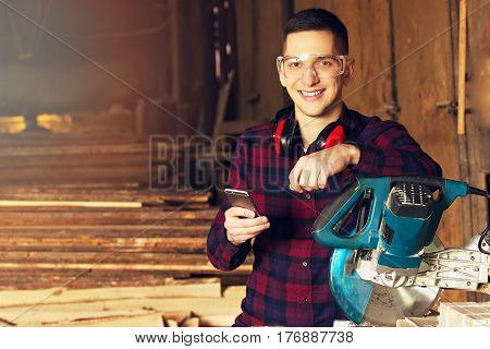 Smiling Workman Dressed In The Checkered Shirt And Wearing Protective Glasses Using His Phone Near T