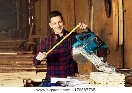 Smiling Workman Dressed In The Checkered Shirt Working With Tape-measure Near Circular Saw At The Sa