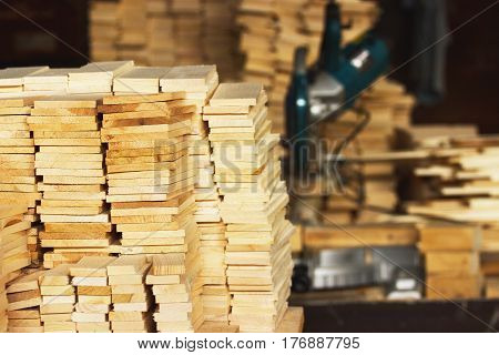 Wood timber construction material closeup for background and texture. Stack of wooden blanks at the sawmill. Circular saw on background.