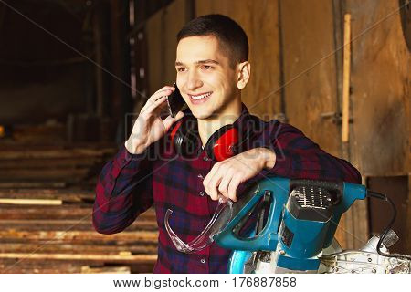 Smiling Workman Dressed In The Checkered Shirt Talking The Phone Near The Circular Saw. Timbers On B