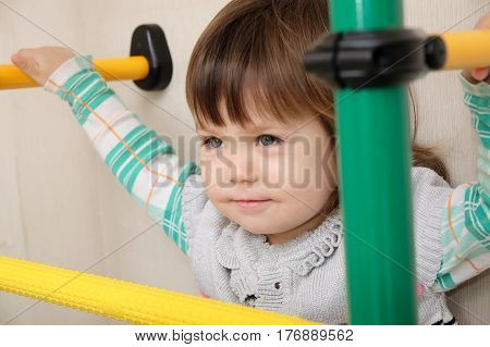 Children home workout. Little girl on gymnastic bar. Child health care and physical training concept. Happy and healthy childhood. Kid on horizontal bar.