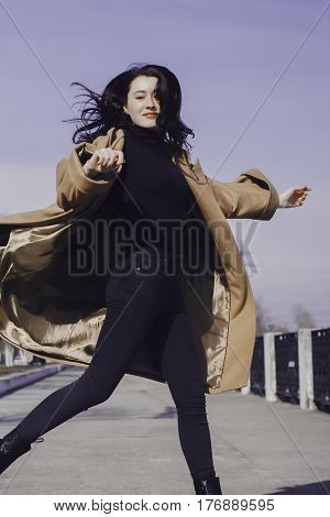 stylish young woman out for a walk. she dressed and looks very fashionable. coat of beige (camel) color and black turtleneck. beautiful woman. She jumps to the side and her hair fly.