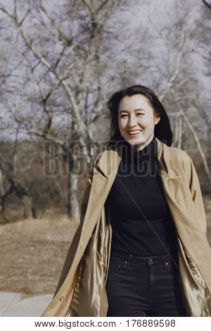 stylish young woman out for a walk. she dressed and looks very fashionable. coat of beige (camel) color and black turtleneck. beautiful woman. the portrait she laughs.
