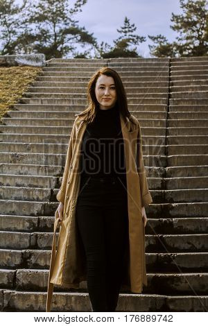 stylish young woman out for a walk. she dressed and looks very fashionable. coat of beige (camel) color and black turtleneck. beautiful woman. She stands at the steps.