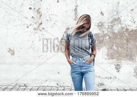 Hipster girl wearing blank gray t-shirt, jeans and backpack posing against rough street wall, minimalist urban clothing style, mock up for tshirt print store