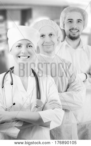 Group portrait of mixed aged medical doctors standing in hospital, looking at camera and smiling. Two men wearing surgeon coat and woman wearing white cap and coat. Focus on woman doctor.
