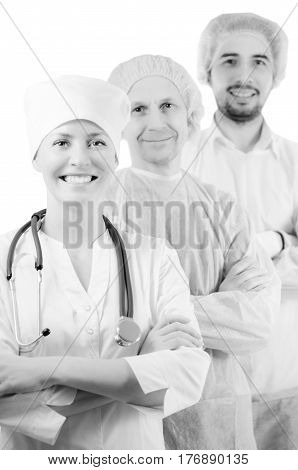 Group portrait of mixed aged medical doctors standing in hospital, looking at camera and smiling isolated on white background. Two men wearing surgeon coat and woman wearing white cap and coat.