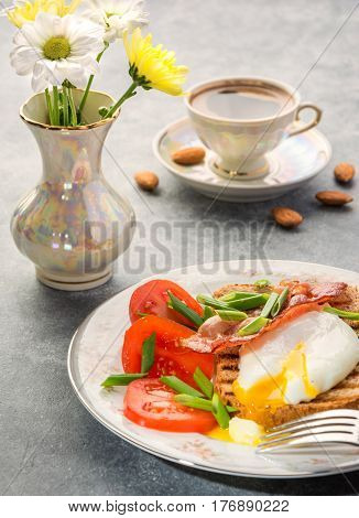 Delicious healthy and nutritious breakfast with egg poached whole-grain toasted bacon tomatoes and coffee with almonds