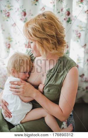 Caring young mother breastfeeds adult baby daughter