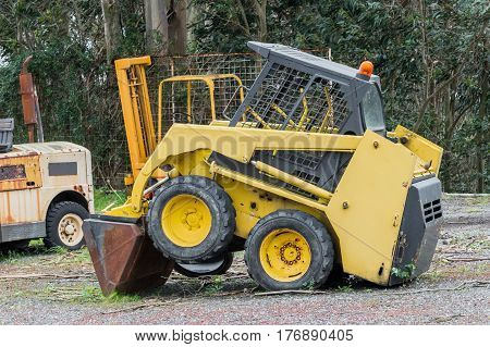 image of yellow excavator in a grader parked