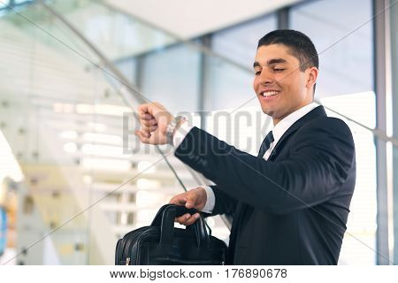 Businessman talking on phone looking at his watch standing on stairs