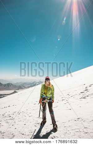 Woman alpinist climbing in high mountains glacier Travel Lifestyle success concept adventure active vacations outdoor mountaineering sport alpinism equipment sunny day