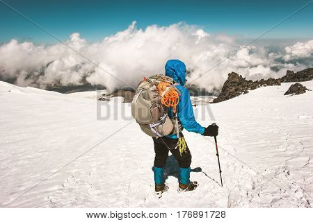 Man alpinist climbing with backpack in mountains glacier clouds Travel Lifestyle endurance concept adventure active vacations outdoor mountaineering sport alpinism equipment