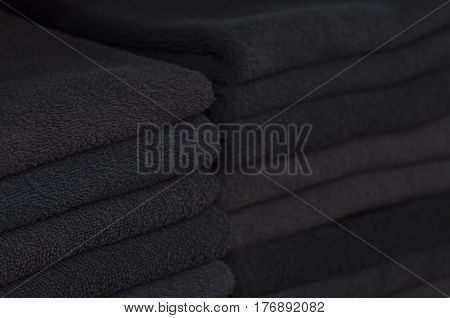 Two piles of black towels laying in the closet