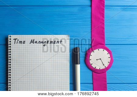 Notebook Marker and Watch on Wood Table Background