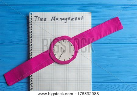 Notebook and Watch on Wood Table Background