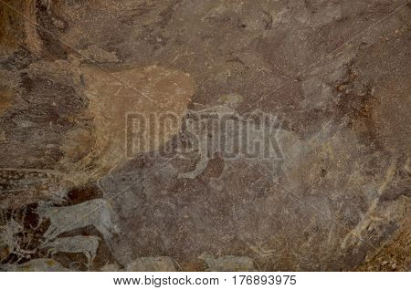 Bhimbetka rock shelters, Madhya Pradesh, India- January 22, 2016:  A Prehistoric Rock Painting showing lots of animals and a men with a Baby elephant at Bhimbetka UNESCO World Heritage Site at Raisen, Madhya Pradesh, India.