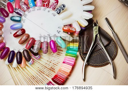 Table full of manicure utensils, manicure tools, nail polish colours on palette. Nails art accessories white. Top View