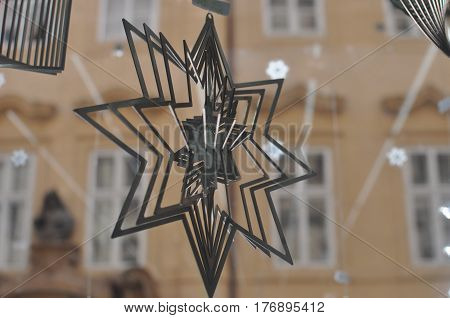 A metal figured snowflake is spinning around its axis