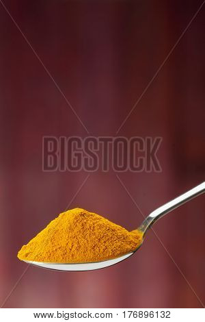 Spoon Of Ground Turmeric On Maroon Background