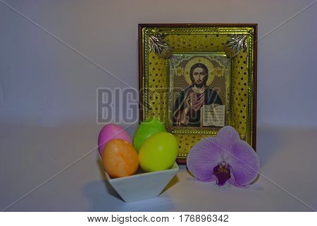 On a white background a composition from the icon of Christ painted eggs in a stand and a flower of an orchid as a symbol of joy and a holiday of Easter.