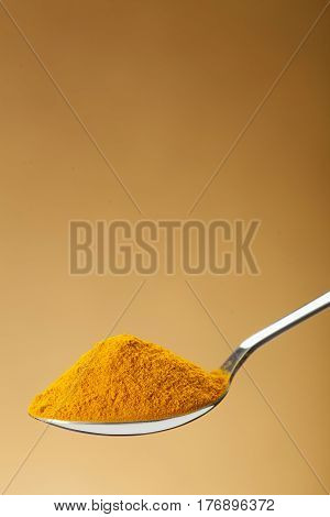 Spoon Of Ground Turmeric On Yellow Background