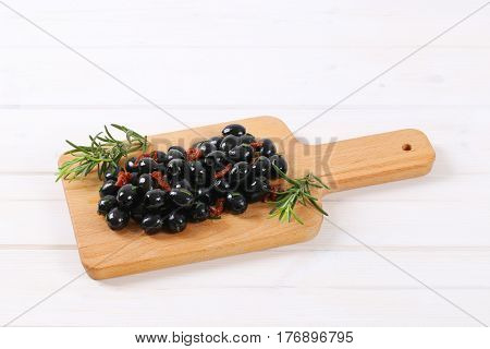 pile of black olives with dried tomatoes on wooden cutting board
