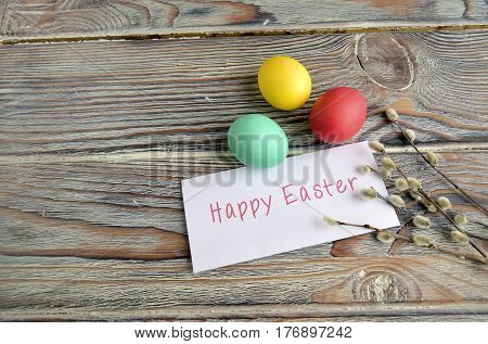 Easter color eggs and willow are a holiday symbol. Eggs, the letter with a wish and a willow are on a wooden table
