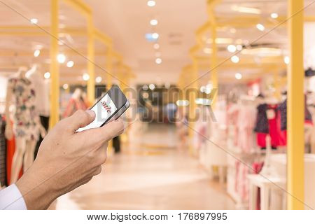 call Hand smartphone blur shopping mall background.