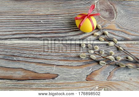 Easter color egg and willow are a holiday symbol. Egg is tied up by a red tape.