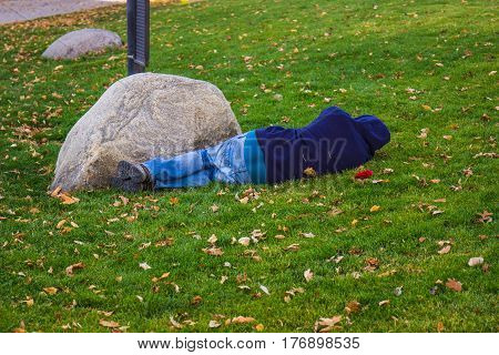 Man Sleeping On The Grass In A Park On A Fall Day