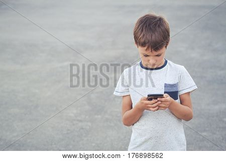 Kid with mobile phone. School, people, technology leisure concept