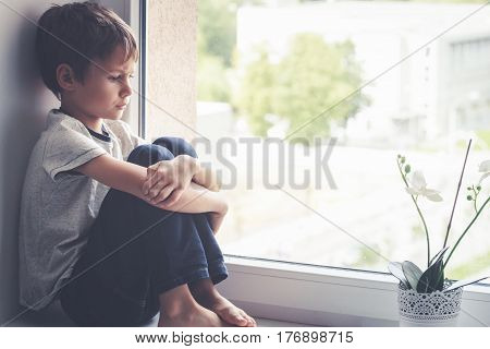 Sad little kid sitting on window shield