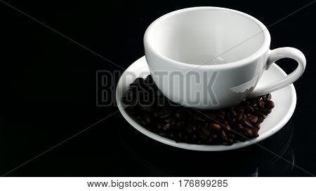 Hot cappuccino with streamed milk. Pour the hot latte art by milk. A cup of strong espresso coffee put on the black glass background with shiny dark roasted Italian coffee beans. Aroma and flavor coffee beverage.