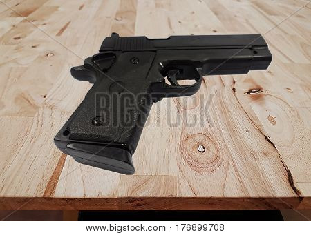 Gun on the wooden background,Model,Toy,weapon,close up short gun model on wooden background.