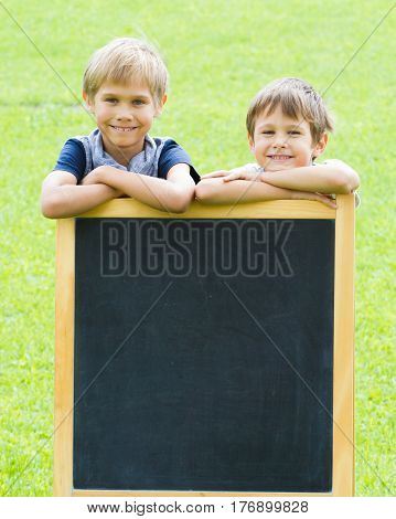 Two boys standing at the blackboard outdoor. Green background. Copy space for text.