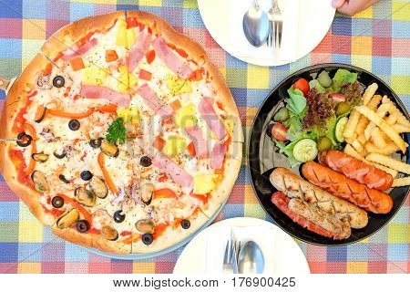 Sausage fried and pizza hawaiian with vegetables on chintz.