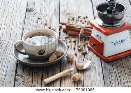 Composition Of Black Hot Coffee In A Cup, Brown Sugar, Coffee Beans And Cardamon Seeds On A Wooden T