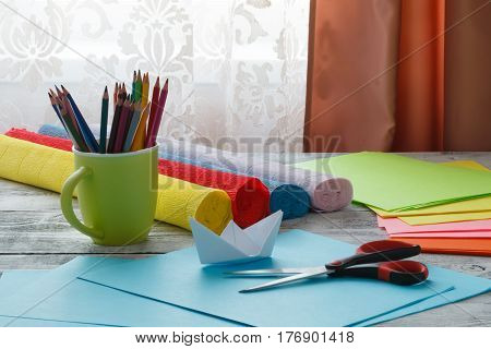 Set Of Origami Boats And Square Sheets Of Colored Paper On A Wooden Table. How To Make A Simple Orig
