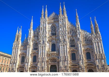 Gothic cathedral facade in Piazza Duomo square of Famous Milan Dome church against a blue sky at midday.Milan Cathedral is a popular landmark and city icon.
