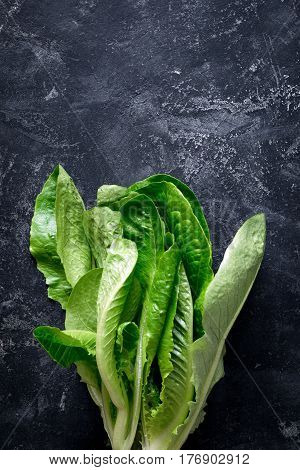 Romaine lettuce salad on slate background, top view with copy space for text
