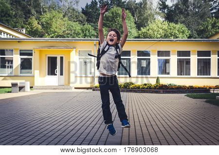Happy kid with backpack jumping and having fun in front of school . Back to School education concept.