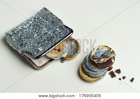 Shiny women's coin purse with chocolate euro coins in it