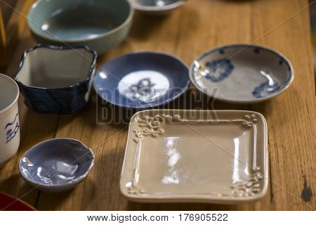 Handmade ceramic dishes on an old vintage table, Sensitive Focus