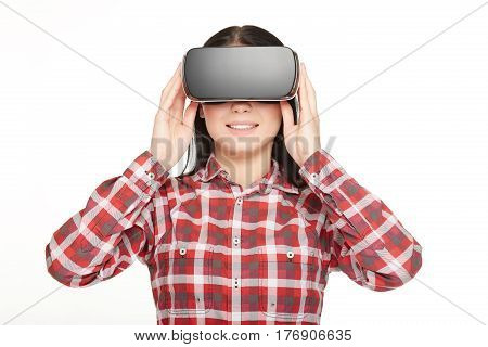 Smiling woman in headset press buttons and watching video with high technology gadget. Beautiful girl in checked shirt spending fun time, wearing glasses of virtual reality and 3d simulation.