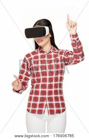 Smiling young girl spending time in virtual reality gesturing and pointing by fingers in air. Stylish woman wearing in headset of VR, playing game, gesturing by hands. Isolate on white.