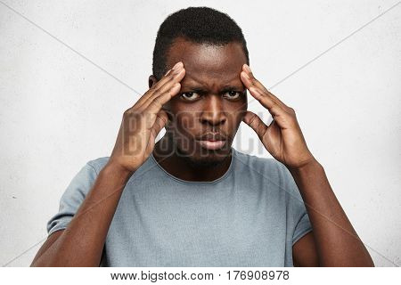 Serious Young Afro-american Man Keeping Hands On Head, Squeezing Temples, Having Bad Headache, Looki